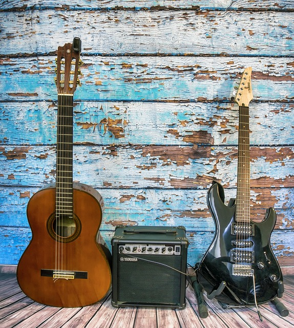 Two guitars, one acoustic and one electric, with an amplifier